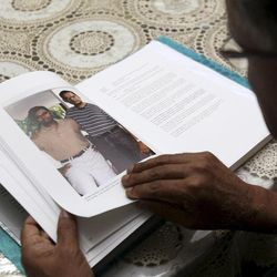 In this photo taken Friday, Sept. 9, 2011, Paramsothy Sivapakiam, 60, father of the 9/11 terrorist attacks victim Vijayashanker Paramsothy, looks at a photo of him and his late son during an interview in Petaling Jaya, near Kuala Lumpur, Malaysia. Sivapakiam said he had to learn to deal with burning hatred and anger against the terrorists who took his son's life.
