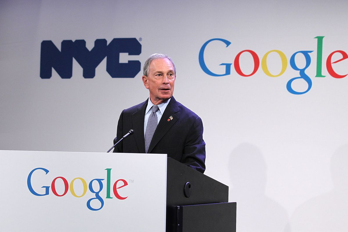"""Mike Bloomberg appears on a podium that says """"Google"""" on it."""