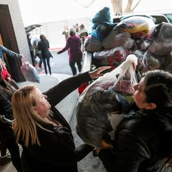Nicole Hudson, bottom left, Evelyn Bojorquez, right, and other Check City employees deliver coats collected during the company's Warm Hearts Coat Drive to the men's resource center in South Salt Lake on Tuesday, Dec. 3, 2019.