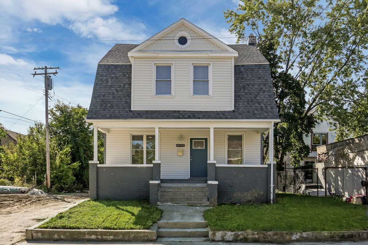 A two-story home with white vinyl siding and gray-painted brick. There's a large dormer window.