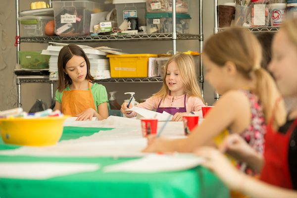 Children are seated at a table doing arts and crafts.