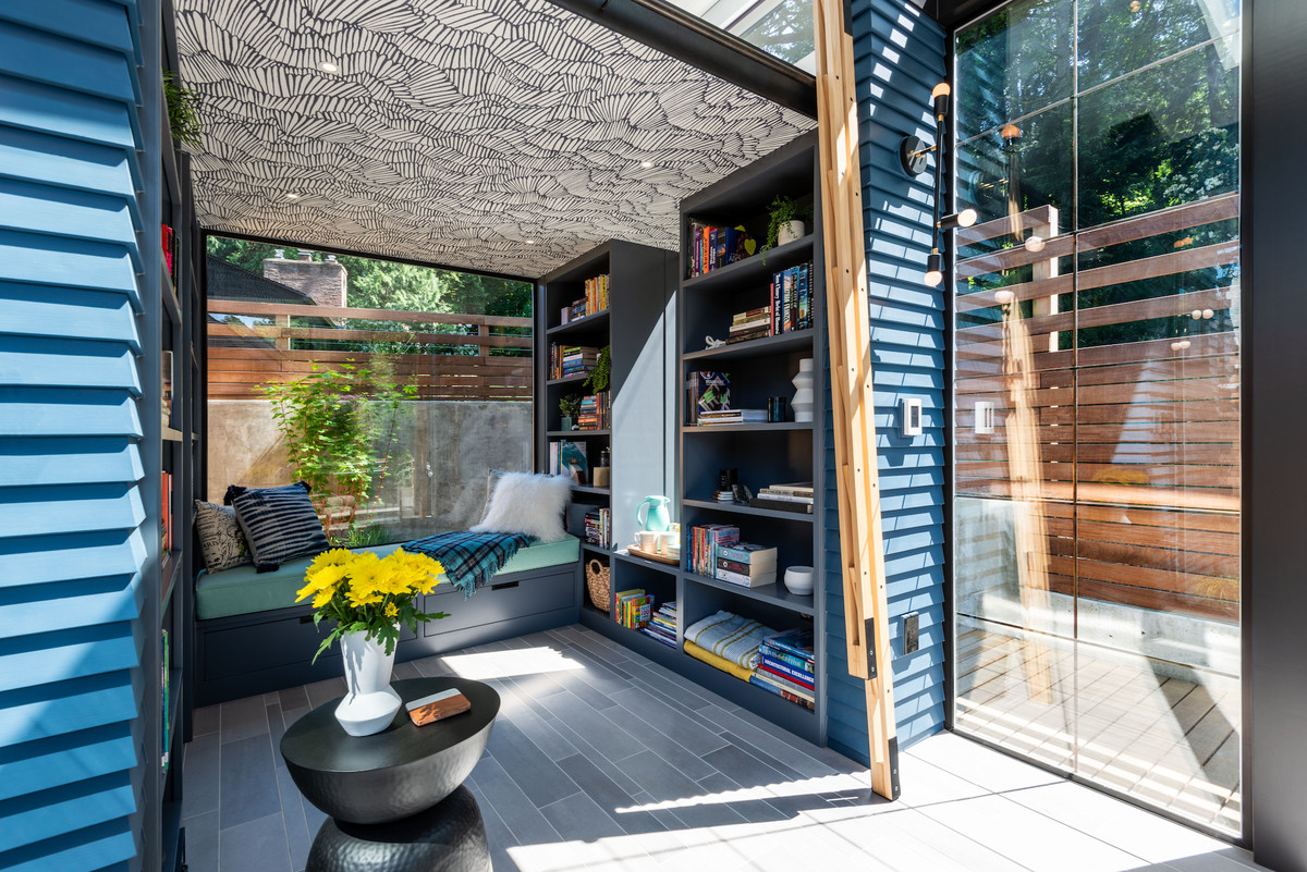 Sunroom of tiny shed leading to bookshelves and daybed
