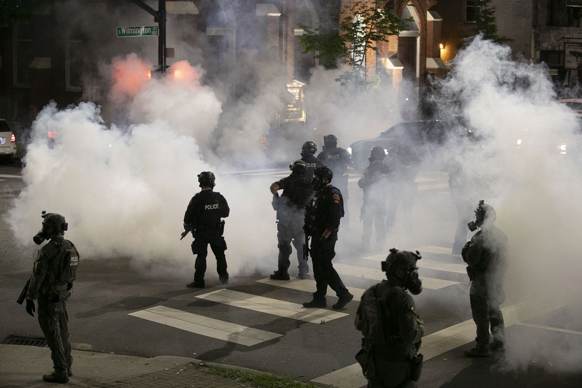 Police in riot gear standing in clouds of tear gas on the stret of Raleigh.