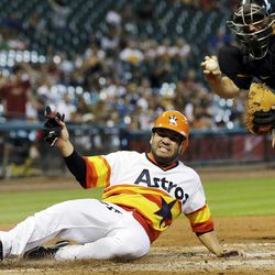 Pittsburgh Pirates catcher Rod Barajas, right, holds out the ball after tagging out Houston Astros' Jose Altuve, left, at a home plate during the third inning of a baseball game, Sunday, Sept. 23, 2012, in Houston.
