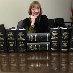 """FILE - In this Thursday, Jan. 9, 2014 file photo, National Taxpayer Advocate Nina Olson poses with tax code books at the Internal Revenue Service in Washington. Olson calls identity theft """"an invasive crime that can have a traumatic emotional impact."""" She said has called on the IRS to designate a single point of contact who can provide """"sensitive, holistic assistance"""" to an identity theft victim."""