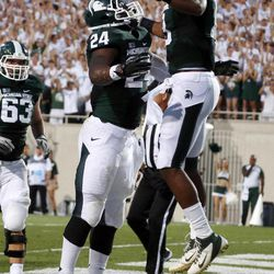 Michigan State's Le'Veon Bell (24) and Bennie Fowler (13) celebrate Bell's first-quarter touchdown against Boise State in an NCAA college football game, Friday, Aug. 31, 2012, in East Lansing, Mich.