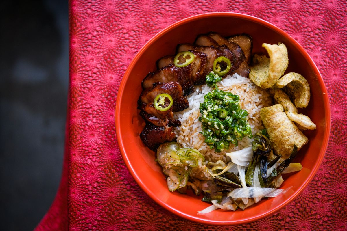 A bowl is filled with aromatic rice, green-dusted pork rinds, thinly sliced alliums, and caramelized hunks of pork.