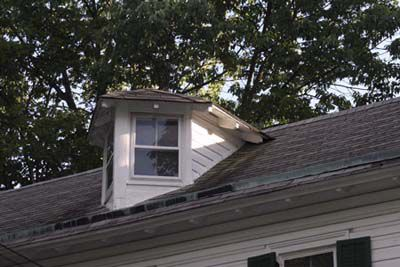 A dormer that has a pyramid-like shaped with sharp edges and windows on either side.