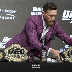Conor McGregor adjusts his belts Thursday at the UFC 229 press conference in New York at Radio City Music Hall.