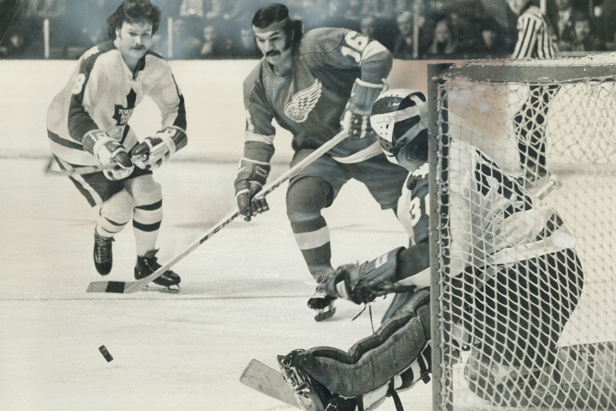 Dunc Wilson; Maple Leafs' goalie; kicks out puck as teammate Jim McKenny and Detroit Red Wings' Henr