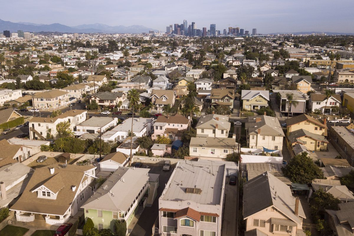 Aerial view of multi-family buildings and large single family homes sprawling for miles before a cluster of tall buildings and a mountain range.