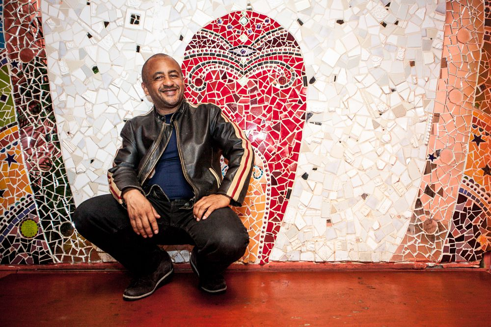 A smiling Marco Senghor, in a leather jacket, squats in front of a mosaic at his SF restaurant in 2014