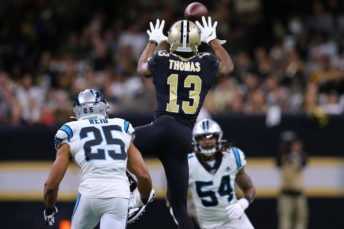 Michael Thomas #13 of the New Orleans Saints catches the ball as Eric Reid #25 of the Carolina Panthers and Shaq Thompson #54 defend during a game at the Mercedes Benz Superdome on November 24, 2019 in New Orleans, Louisiana.