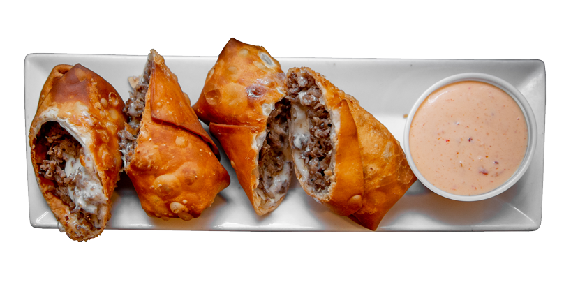 Overhead view of a long white plate with four diagonally cut, large pieces of deep-fried egg roll stuffed with meat, with a white-ish-pink dipping sauce to the side