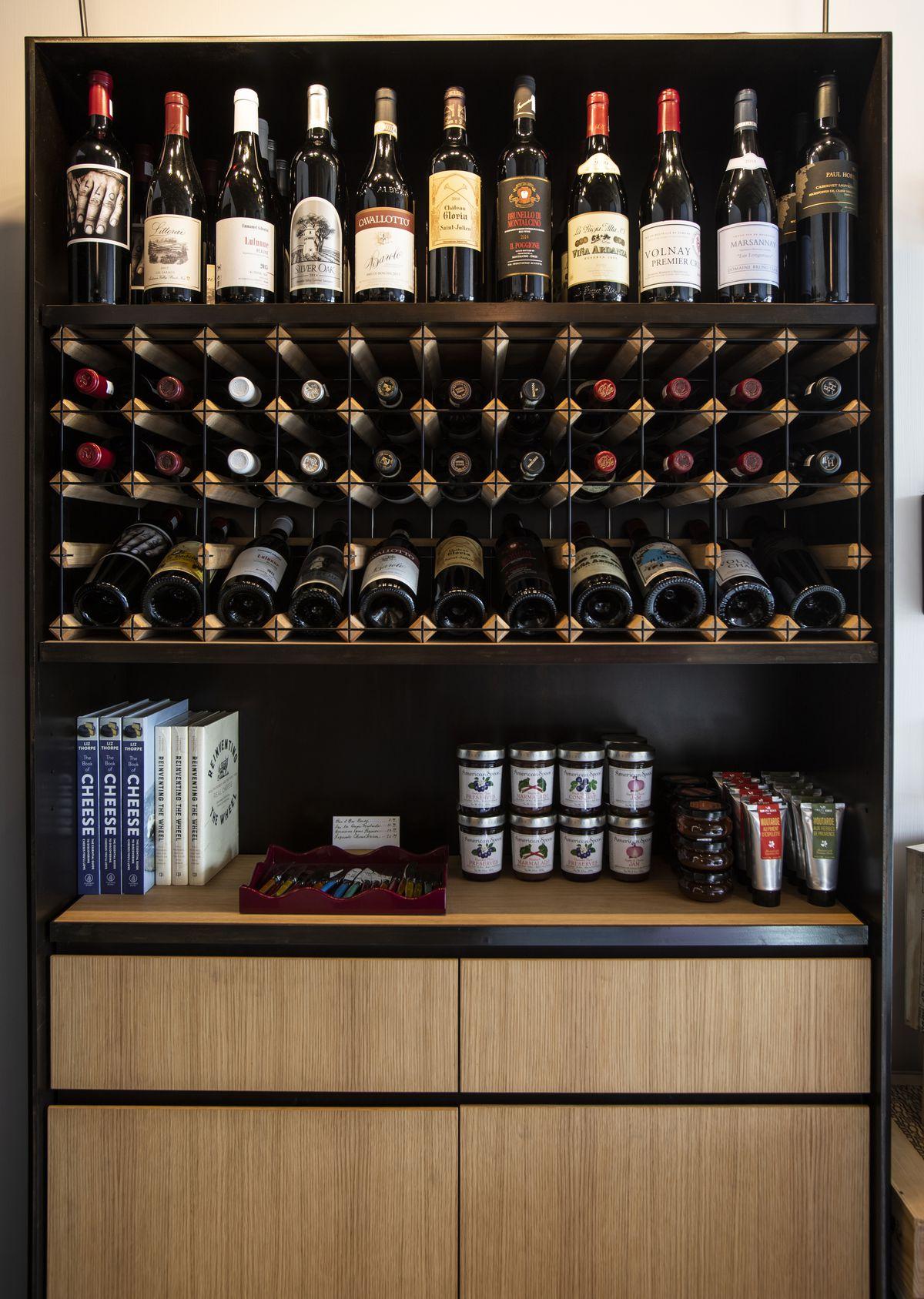 Các chai rượu nằm ngang trong giá rượu trên mặt phản gỗ.