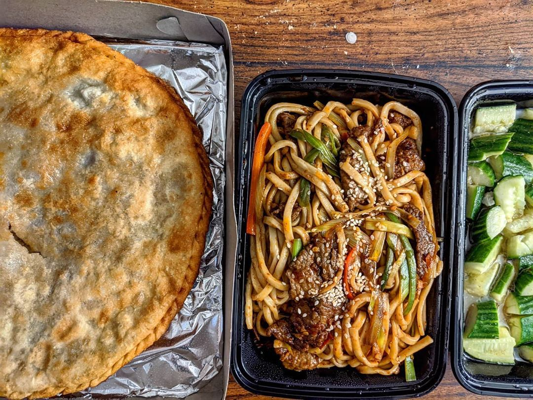 Overhead view of takeout Uyghur cuisine: a round of stuffed naan in a pizza box, a noodle and beef dish, and chopped cucumbers