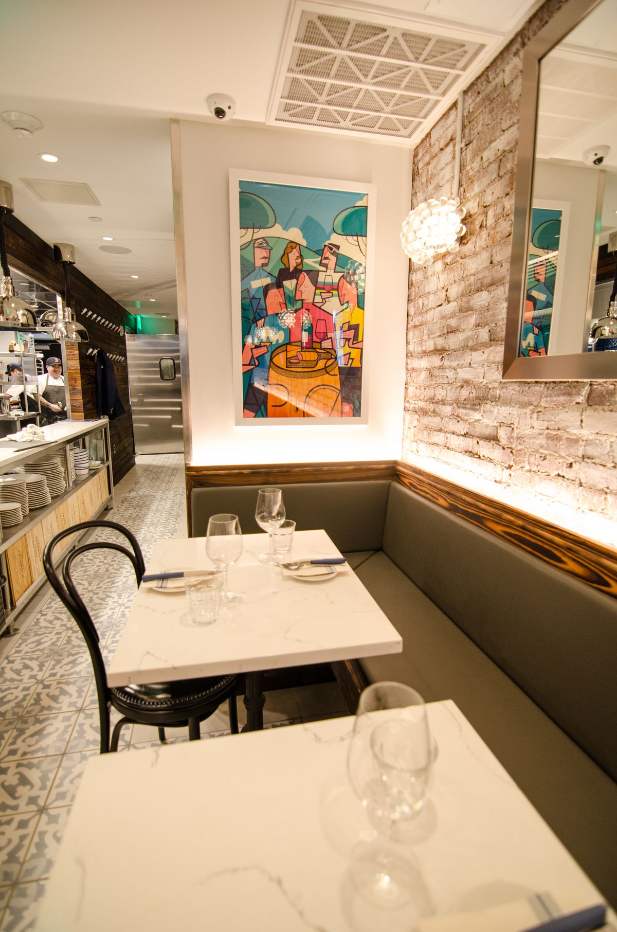 Closeup of a colorful piece of artwork inside a restaurant with white marble tables and a Spanish-style tiled floor