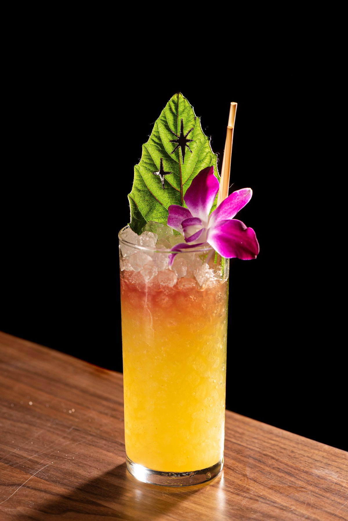 A tall, colorful cocktail in a dark room.