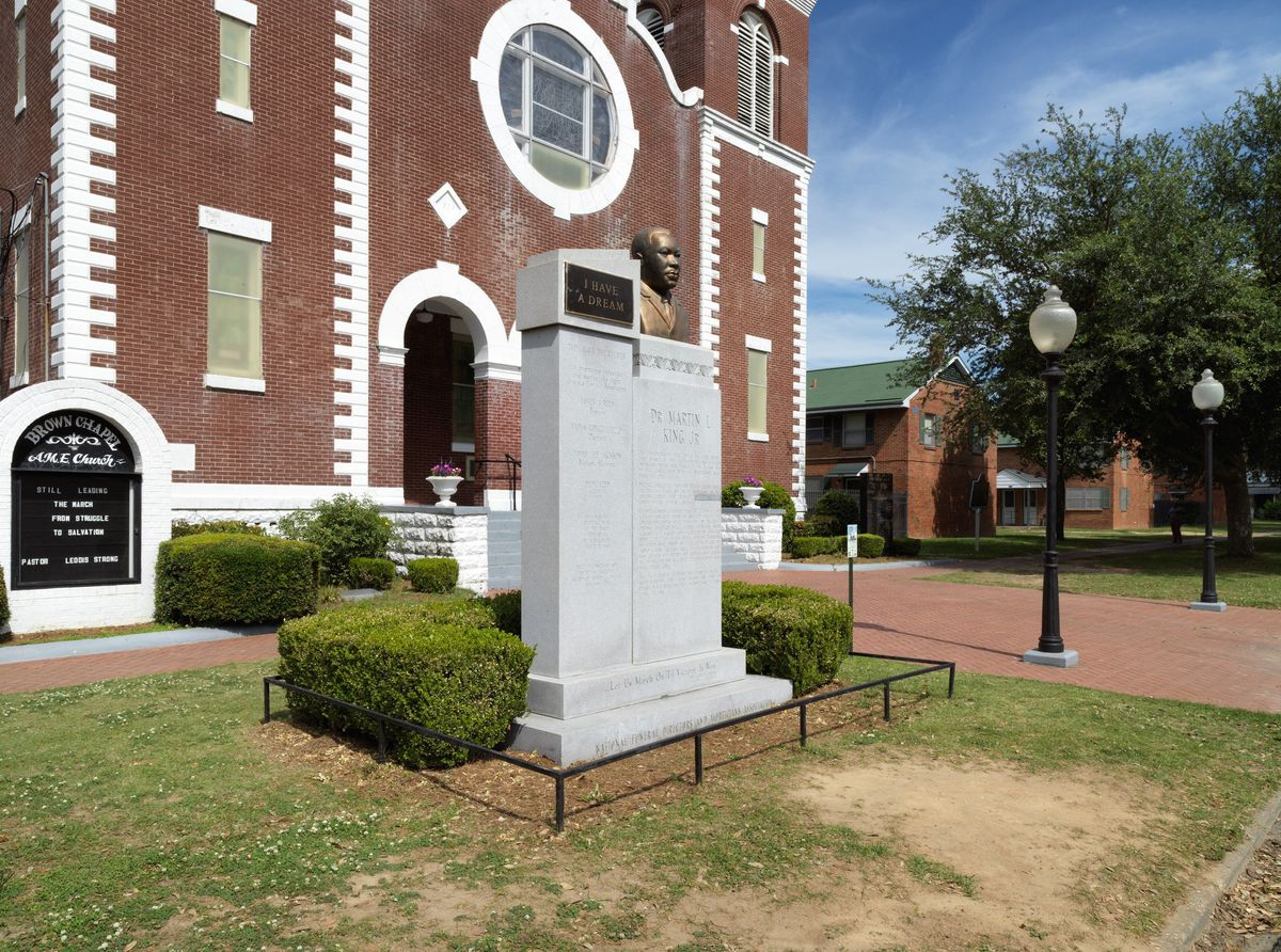 The exterior of a southern church, built in red brick with white trim.