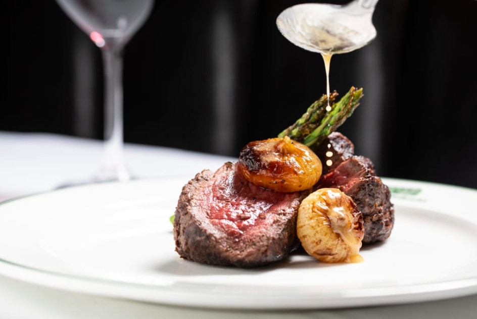 A spoon drizzles sauce over a cut of steak, onions, and asparagus