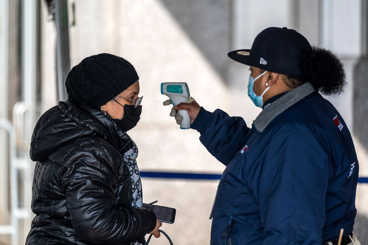 A woman has her temperature checked before receiving her coronavirus vaccine at Yankee Stadium, Feb. 5, 2021.