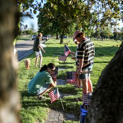 Volunteers place flags at Larkin Sunset Gardens Cemetery in Sandy on Thursday, May 27, 2021. More than 200 youth volunteers from around the Salt Lake Valley honored military veterans for Memorial Day by placing 3,000 American flags on the graves of service members. In addition, they swept and polished headstones and helped beautify cemetery grounds.