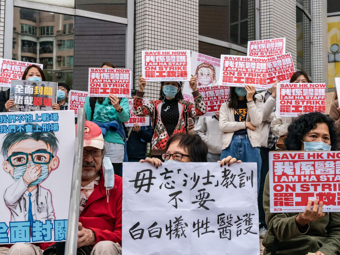Medical workers in Hong Kong holding protest signs that refer to the coronavirus outbreak.