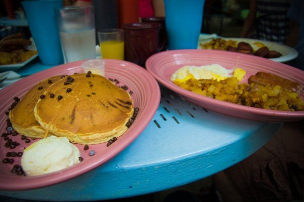 A blue outdoor table is covered with large plates of breakfast food. Two pink plates in the foreground hold chocolate chip pancakes, hashbrowns, egg, and sausage.