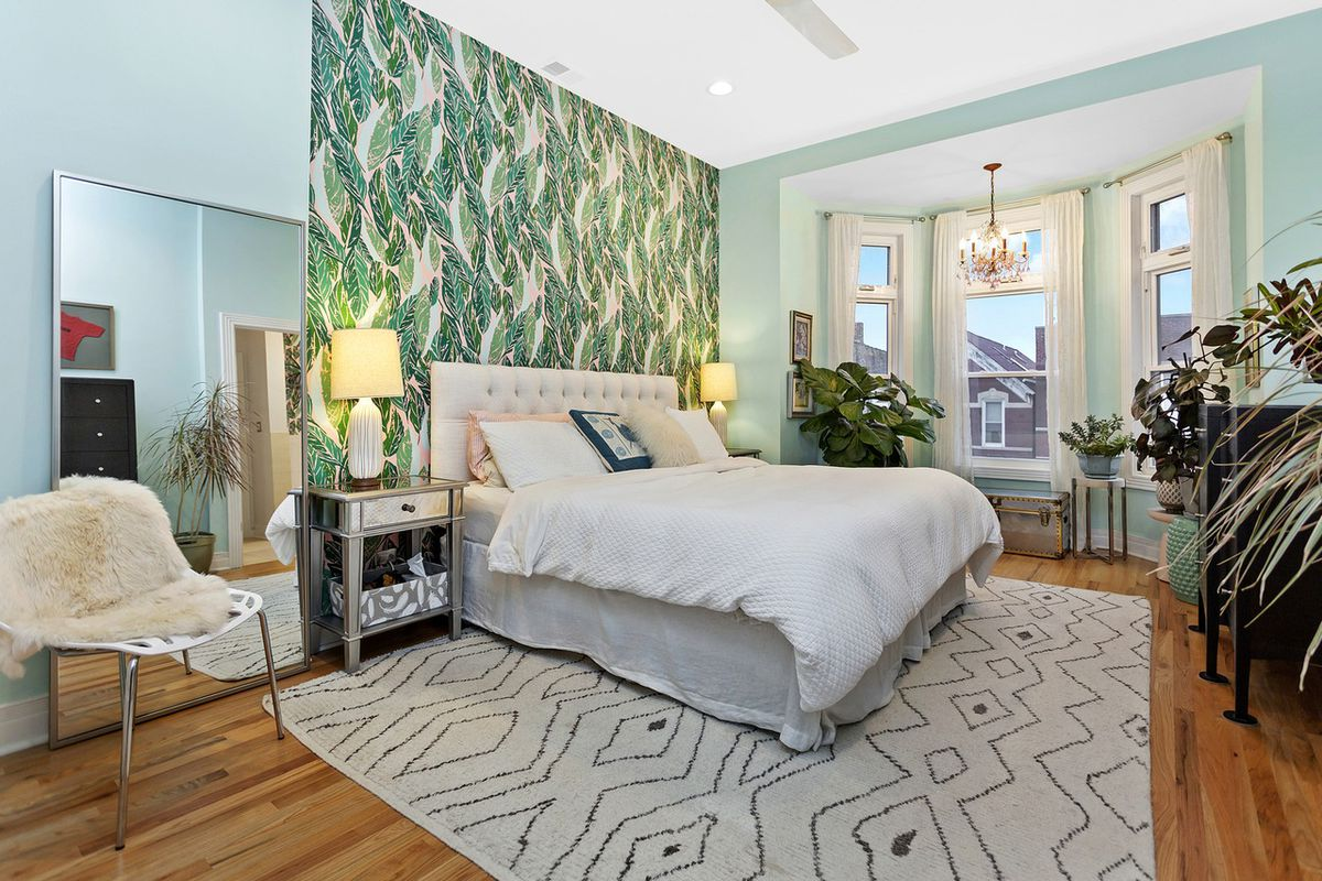 A master bedroom with a floral accent wall and a three-part bay window overlooking a residential street.