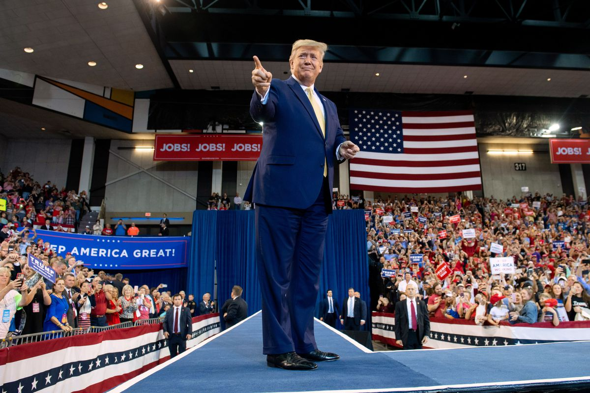 Trump smiles and points in front of a US flag surrounded by a crowd of cheering supporters.