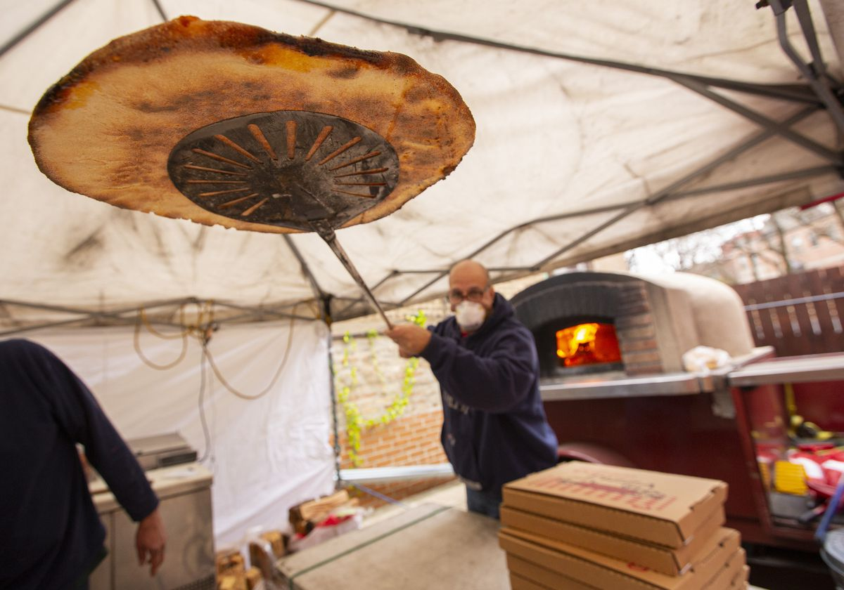 A man lifts a pizza out of an wood-burning oven outside.