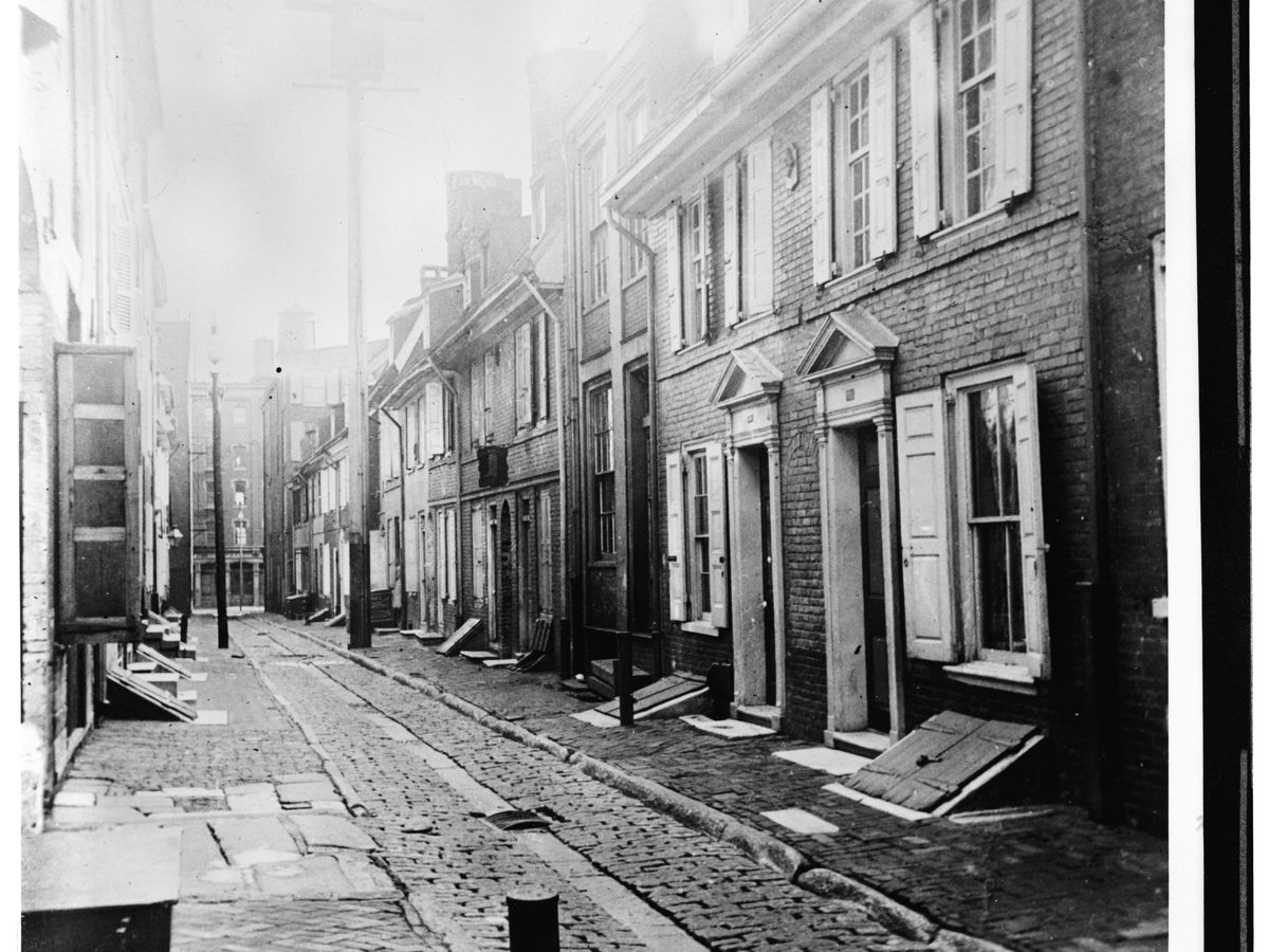 The exterior of Elfreth's Alley in Philadelphia. The buildings that line the street are brick with window shutters. This is an old black and white photograph.