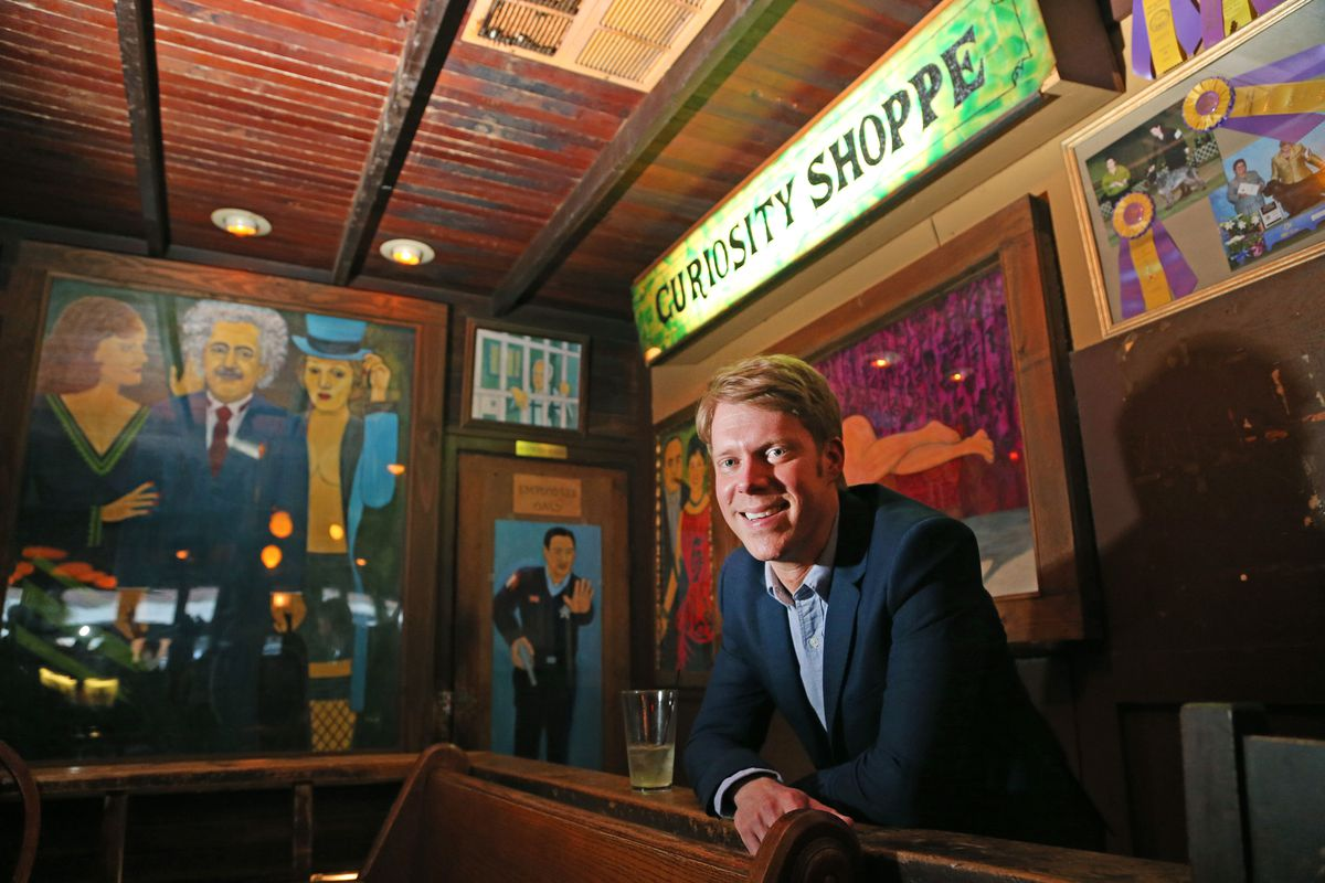 """A man leans on a wooden bar under a sign that says """"Curiosity Shoppe.'"""" There are cartoonish paintings of people on the wall."""