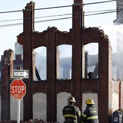 Firefighters view the aftermath of a fire in a warehouse on York Street near Kensington Avenue in Philadelphia on Monday, April 9, 2012. Two firefighters died after a wall collapsed on them while they fought the massive early-morning blaze.