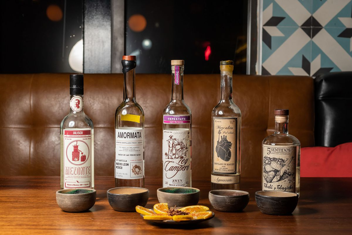 Five select artisan bottles from Madre in Torrance lined up with sliced oranges and chapulines.