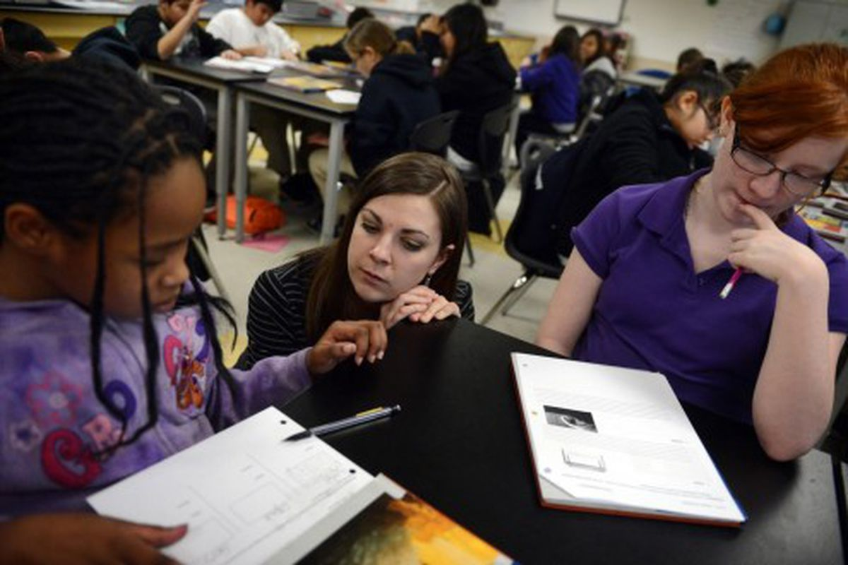 A sixth grade science teacher works with students during Kearney Middle School in 2013 (Denver Post file)