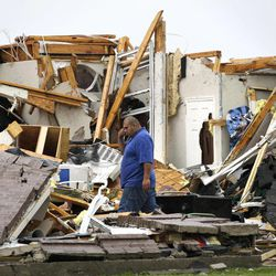 Juan Ventura stands inside what remains of his home as he talks with his father on his mobile phone Tuesday, April 3, 2012, in Forney, Texas. Ventura said that no one was home when the storm hit.