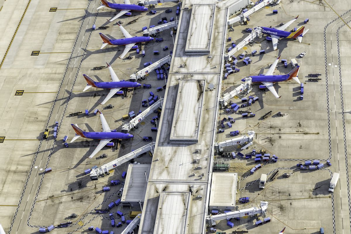 An aerial view of a terminal at the airport with six planes parked different gates along a long terminal.