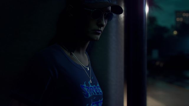 A woman in a ballcap and sunglasses peeks around the corner at the viewer