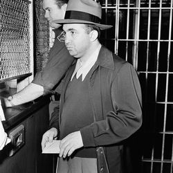 """Being booked on conspiracy to commit murder in 1949. Photo via the <a href=""""http://bigstory.ap.org/content/mickey-cohen-0"""">AP</a>."""