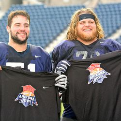 USU offensive linemen Quin Ficklin, left, and Roman Andrus show off their new T-shirts from the NOVA Home Loans Arizona Bowl after the Aggies' practice on Dec. 19 at Maverik Stadium in Logan.