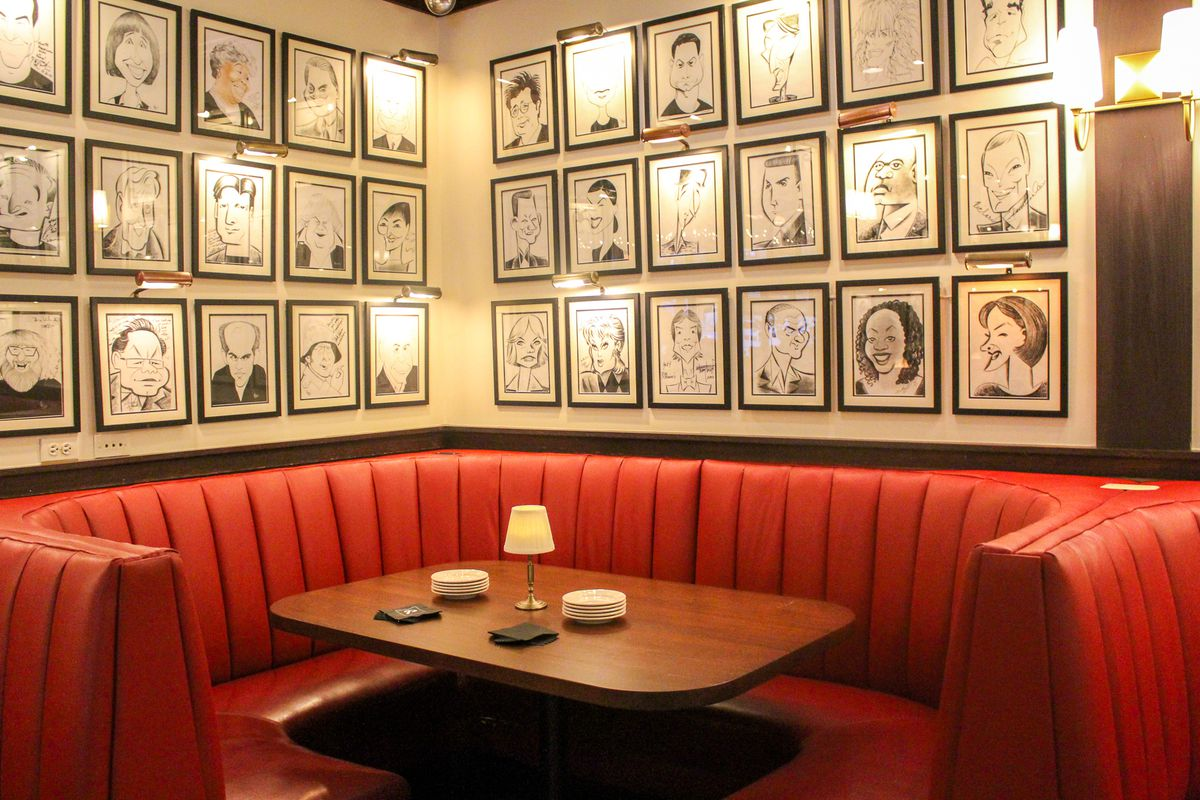A red leather corner booth with a wooden table in the middle with framed pictures on the wall above