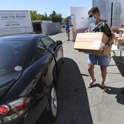 Salt Lake City Mission volunteers Rose Eyre, center, and Raymette and Rick Francom, help load boxes of food into a car during the mission's Father's Day Food Box Giveaway in Salt Lake City on Friday, June 19, 2020. The mission is providing relief to families suffering financial loss due to the COVID-19 pandemic. The volunteers loaded food boxes into cars as they drove up to the mission's Salt Lake location at 1151 South Redwood Road.