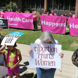 Women pray in the foreground as Planned Parenthood supporters hold a banner in the background as a group called Women Betrayed holds a rally to support ending taxpayer funding of Planned Parenthood in front of the Planned Parenthood offices, July 28, 2015, in Salt Lake City.
