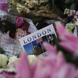 A postcard is placed between flowers on a memorial for victims in the London Bridge area of London, Tuesday, June 6, 2017. British police on Tuesday named the third London Bridge attacker as an Italian national of Moroccan descent, and Italian officials said they had passed on their concerns about him to British intelligence officials last year.