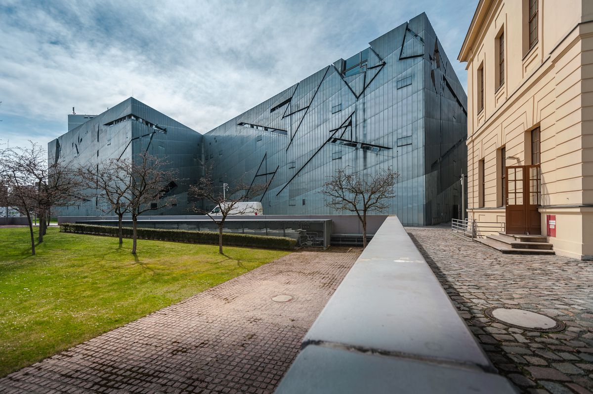 The exterior of the Jewish Museum Berlin. The facade consists of angled dark grey glass.