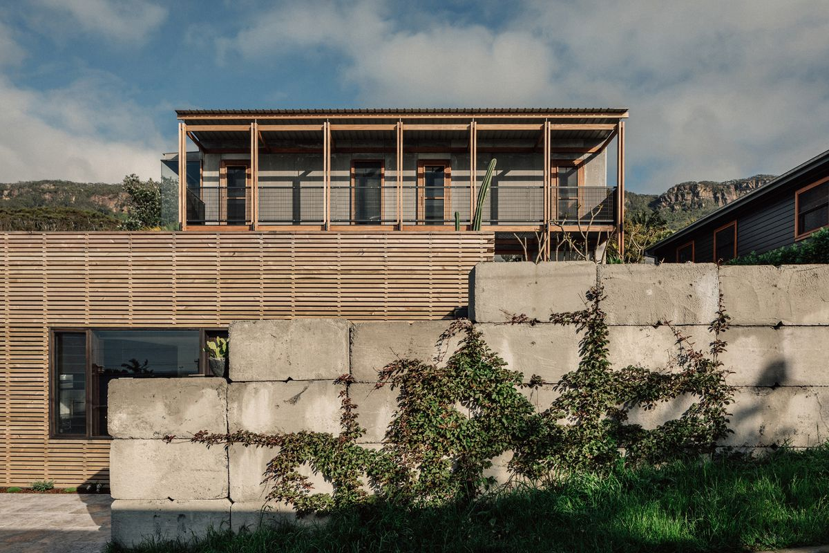 Concrete block wall shielding wood and concrete-clad home.