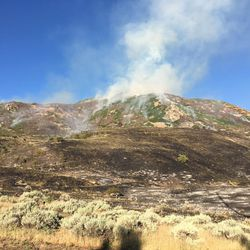 Winds are blowing a brush fire uphill and away from homes above Farmington, officials said.