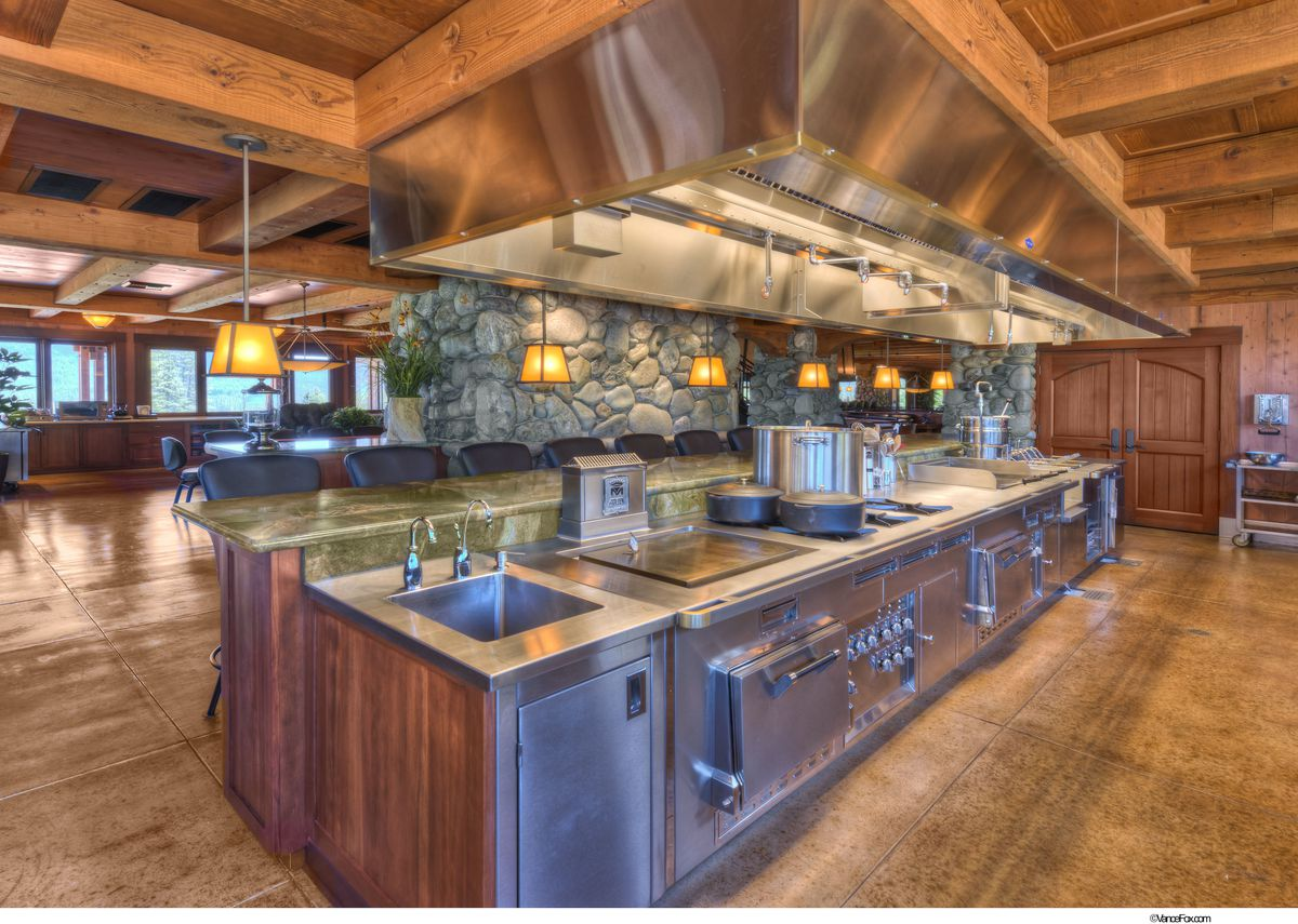 A large industrial kitchen features stainless steel and river rock.