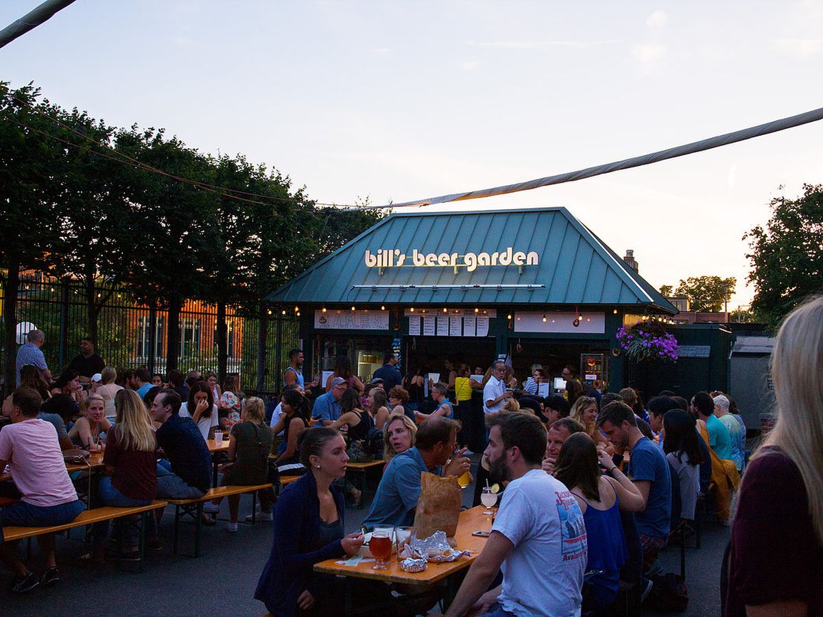 people sitting outdoors at wooden communal tables at twilight. There's a Bill Beer Garden sign on a blue roof in the background.